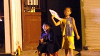 A boy tries to cool himself with a paper fan outside his house in Hanoi during a blackout while his grandmother sits beside him