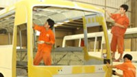 Workers paint a bus frame at a subsidiary of state-owned automobile company Vietnam Motors Industry Corporation.