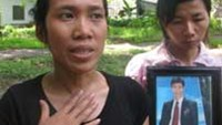 Nguyen Thi Thanh Tuyen, 30, shows a photo of her husband, 33-year-old Nguyen Cong Nhut, who died in police custody last month.