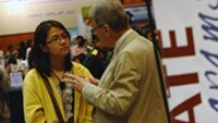 A Vietnamese student talks with a staff member of a US college during an education fair in Hanoi.