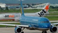 A Vietnam Airlines aircraft taxying next to an aircraft owned by low-cost airline Jetstar Pacific at Hanoi's Noi Bai International Airport.