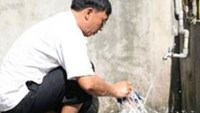 Former drug addict Nghia does house chores at home in Hai Phong City.