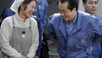 Japan's Prime Minister Naoto Kan (R) bows as he speaks to tsunami victim Ryoko Otsubo during his visit to an evacuees shelter in Rikuzentakata, after the area was devastated by a magnitude 9.0 ear