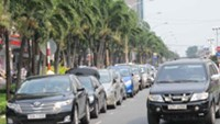Cars parked on a street in Ho Chi Minh City. A new plan to restrict cars from the city's downtown area based on odd or even number plates has been criticized as impractical.