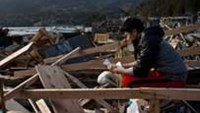 A Japanese student searches for prized possessions in the rubble of his family home in Ishinomaki, Miyagi Prefecture.