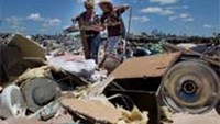 A couple try to salvage items from a flattened shop in Tuscaloosa, Alabama.
