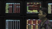 An investor smiles as she walks past screens showing stock information at a brokerage house in Wuhan, Hubei province June 24, 2011.