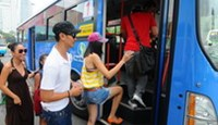 Vietnamese singers and movie stars boarding a bus to Ho Chi Minh City's Binh Tay Market to promote public transportation