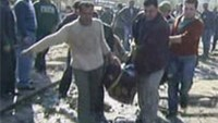 An image grab taken from Syrian state TV shows Syrians carrying away a dead body at the site of a suicide attack outside a security service base in Damascus.