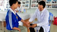A boy suffering from dioxin poisoning being examined at a clinic in Da Nang.