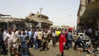 Iraqi rescue and security personnel inspect the damage following a truck bomb in a crowded market in Diwaniya.