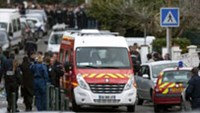 Police officers and firefighters gather at the site of a shooting in Toulouse, southwestern France, Monday, March 19, 2012.