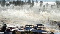 A tsunami wave engulfs a residential area after a powerful earthquake in Natori, Miyagi Prefecture, Japan, on March 11