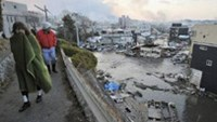 Houses swept by a tsunami are seen as residents walk in Kesen Numa, Miyagi prefecture March 12, 2011
