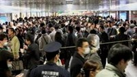 Commuters stand in line to board other trains at Yokohama Station, southwest of Tokyo, March 14, 2011