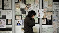 A Japanese tsunami survivor stands in front of messages displayed on the wall of a relief center in Rikuzentakata, Iwate prefecture.
