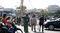 Tourist police help foreigners cross the street in Ho Chi Minh City
