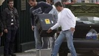Plain clothes policemen carry equipment into the Russian embassy following an explosion in Athens November 2, 2010.