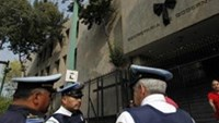 People stand outside Mexico's Interior Ministry which bears a black ribbon in a sign of mourning in Mexico City November 11, 2011.