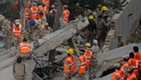 Relief workers carry out rescue operations amidst the rubble in eastern New Delhi on November 16, 2010 after a building collapsed.
