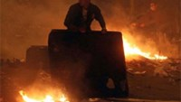 An Egyptian protester tries to put out a fire at Cairo's Tahrir Square during clashes with security forces.