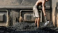 A miner is seen here unloading coal from a train, in eastern China.
