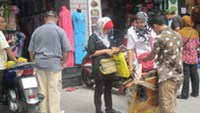 A street vendor with to two foreign tourists in Ho Chi Minh City. Photo by Bach Dang