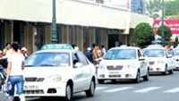 A line of unlicensed taxis on a Ho Chi Minh City street