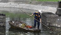 A worker collects garbage from the Hale Lake in Hanoi April 17. Photo: Reuters