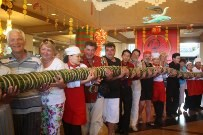 Several foreign tourists give their hands to Yasaka Saigon Nha Trang Hotel to prepare the 37-meter long banh tet