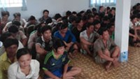 The gamblers who were arrested at a cockfight in HCMC Sunday being held in a police station in Binh Chanh District (Photo: Tuoi Tre)