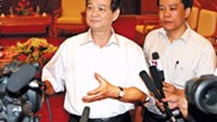 Prime Minister Nguyen Tan Dung (left) talks with the press July 1 after a regular cabinet meeting.