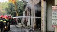 Firefighters extinguish a fire at a retail cooking gas outlet in Hanoi in Hanoi on Sunday morning. An explosion in the shop killed a woman and her seven-month-old son.