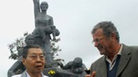 Director Le Dan (L) talks with Saub Gérald, who plays the film's main character, in front of a statue commemorating victims of the My Lai massacre