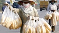 Street vendors carry bread while waiting for customers on a highway in Hanoi.