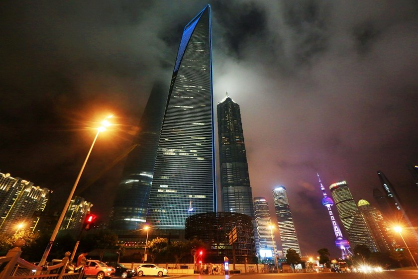 Night view of the Shanghai Tower under construction, tallest left, the Shanghai World Financial Center (SWFC), tallest center, the Jinmao Tower, tallest right, and other skyscrapers and high-rise buildings in the Lujiazui Financial District in Pudong, Sha
