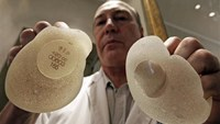Plastic surgeon Denis Boucq poses with silicone gel breast implants manufactured by French company Poly Implant Prothese (PIP) in a clinic in Nice December 26, 2011.