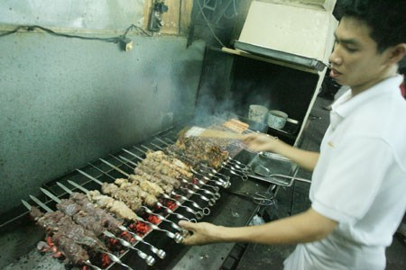 The grill master at Quan Chieu Nay on 30B Vo Van Tan Street adjacent to the War Remnants Museum