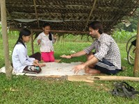 "The author plays a rock game called ""peh"" with two girls between a corn field and buffalo grazing grounds near Pac Ngoi Village in Ba Be National Park in the northern province of Bac Kan. Photo: Olof"