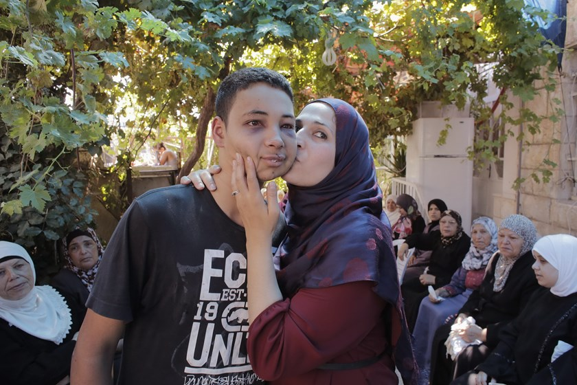 Tariq Khdeir (L) is kissed by his mother in a mourners tent for his cousin Mohammed Abu Khudeir in the Arab neighbourhood of Shuafat in Jerusalem July 6, 2014.
