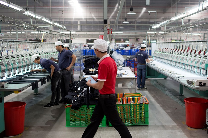 "Workers arrange pieces of fabric under embroidery machines inside a garment factory the southern Binh Duong Province. The poor quality of Vietnam's labor force ""remains a challenge"" to its development. Photo credit: Bloomberg"