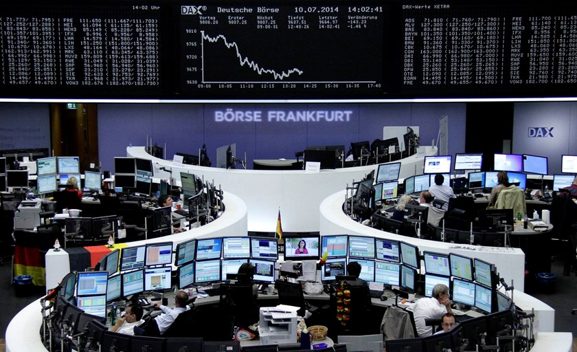 Traders are pictured at their desks in front of the DAX board at the Frankfurt stock exchange July 10, 2014. Photo credit: Reuters