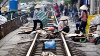 Workers bundle reclaimed materials by the train tracks in Hanoi. Three Japanese execs are facing charges for allegedly bribing Vietnamese railway officials to win work tied to projects funded by Japanese aid. Photo credit: Bloomberg