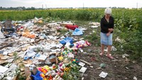 A local resident stands near flowers and mementos placed at the crash site of Malaysia Airlines Flight MH17, near the settlement of Rozspyne in the Donetsk region July 19, 2014. Photo: Reuters