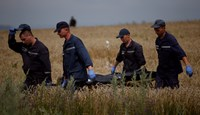 Members of the Ukrainian Emergency Ministry carry a body at the crash site of Malaysia Airlines Flight MH17, near the settlement of Grabovo in the Donetsk region July 19, 2014. Photo credit: Reuters