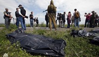 Organisation for Security and Cooperation in Europe (OSCE) monitors and journalists walk as a pro-Russian separatist stands on guard near bodies at the crash site of Malaysia Airlines Flight MH17, near the settlement of Grabovo in the Donetsk region July