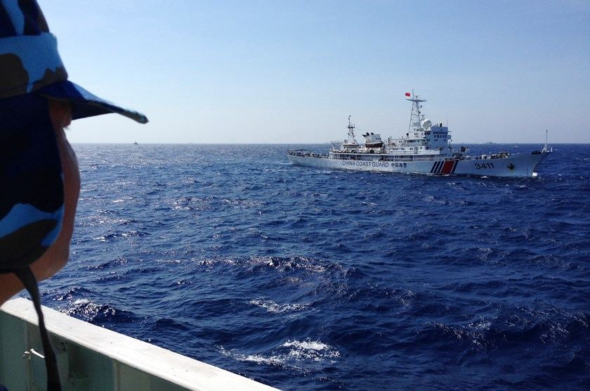An officer on the Vietnamese Coast Guard vessel No. 8003 looks on as it is flanked by a Chinese Coast Guard ship, right, in Vietnamese waters west of the Paracel (Hoang Sa) Islands, on  May 14, 2014. Photo credit: Bloomberg