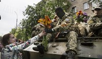 A woman gives flowers to an armed Pro-Russia man riding an armored personnel carrier during celebrations to mark Victory Day in Slaviansk, eastern Ukraine.