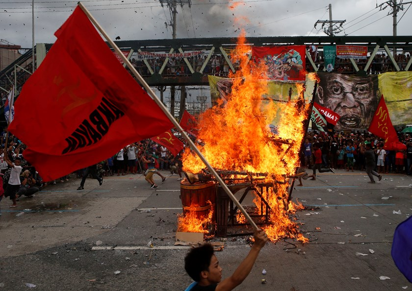Protesters wave protest flags past a burning effigy of Philippine President Benigno Aquino, as Aquino delivers his fifth State of the Nation Address (SONA) during the joint session of the 16th Congress at the House of Representatives of the Philippines in