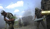 Ukrainian servicemen, who are members of an artillery section, take cover after firing a cannon during a military operation against pro-Russian separatists near Pervomaisk, Luhansk region August 2, 2014. Photo credit: Reuters